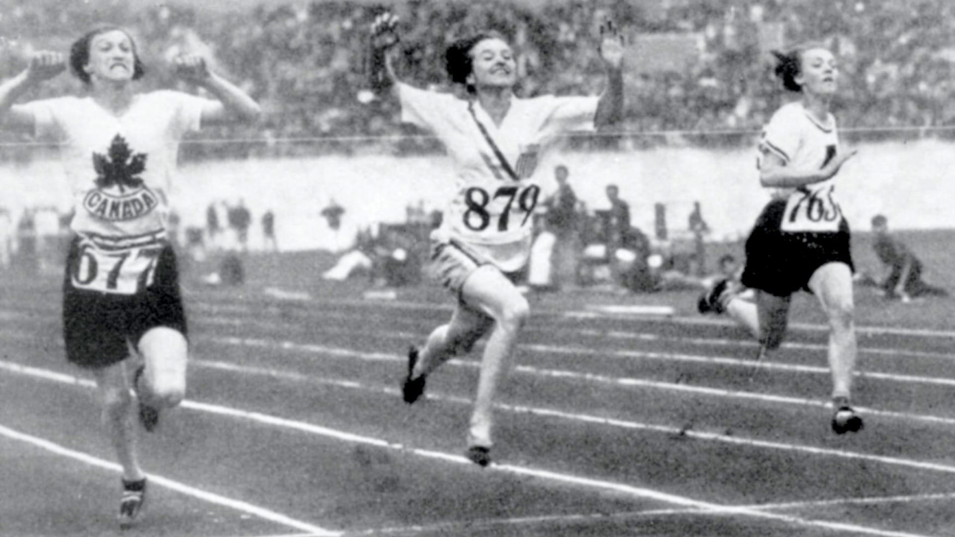 Betty Robinson raises her arms and exults as she crosses the finish line