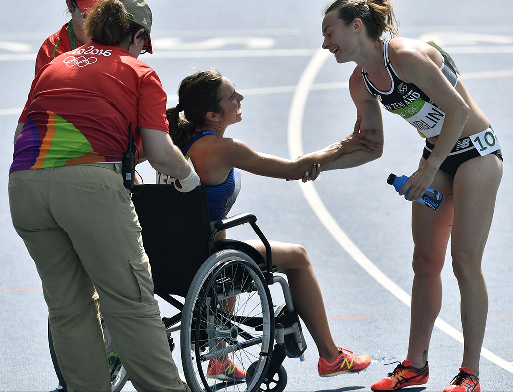 Nikki Hamlin and Abbey D'Agostino (in a wheelchair) share a moment after their race.