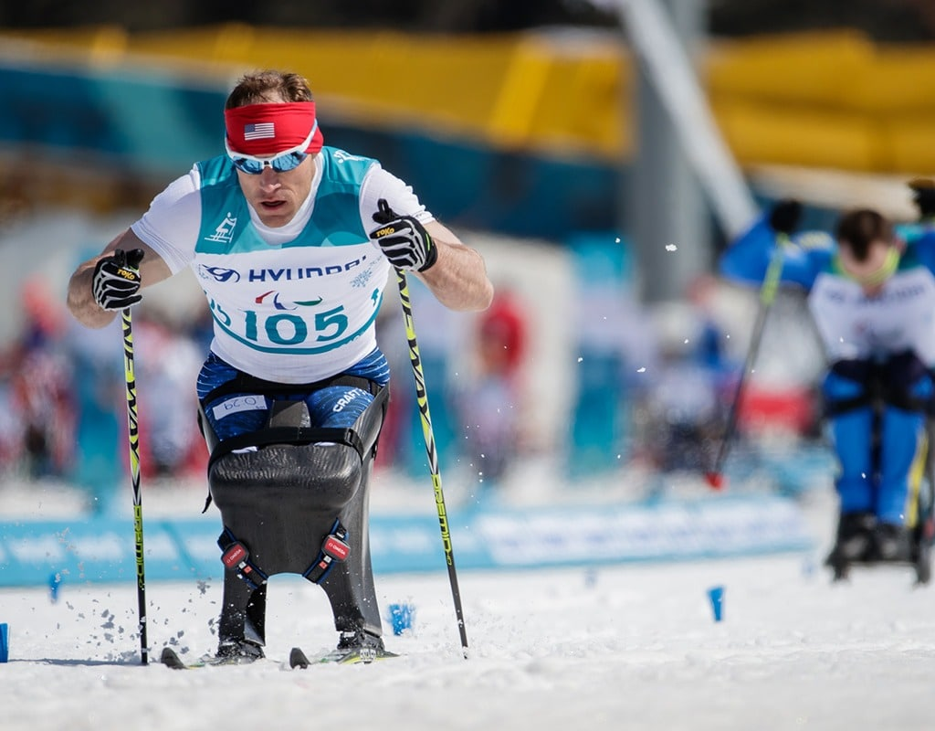 Paralympic athlete Dan Cnossen skiing and pushing his poles into the snow during a biathlon race in the PyeongChang 2018 Paralympic Winter Games.