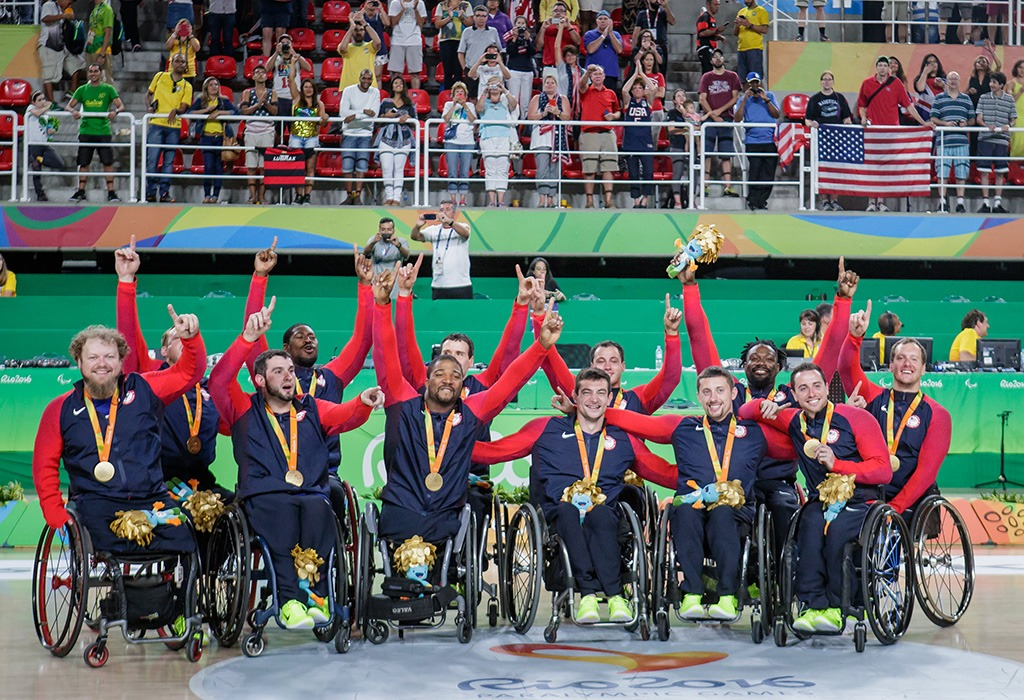The U.S. Men's Wheelchair Basketball Team proudly wears their medals and raises their arms in triumph.