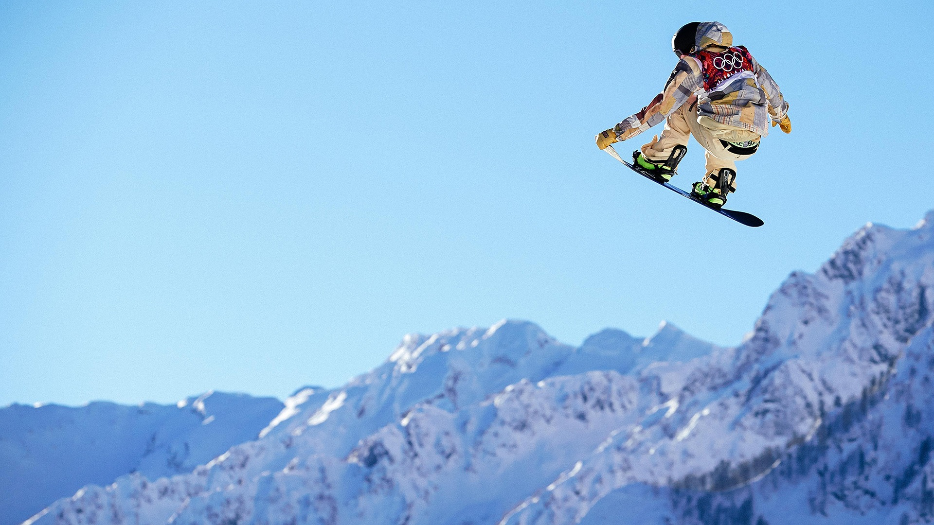 Sage Kotsenburg soars high in the air with mountains in the distance