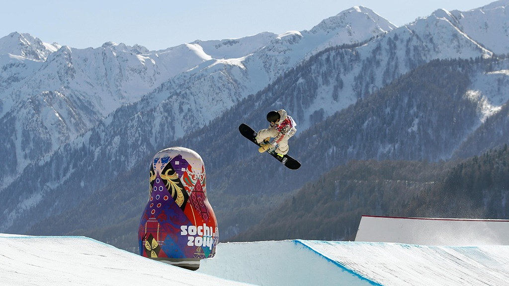 Sage Kotsenburg soars in air over an inflatable Russian doll with snowcapped mountains in the background