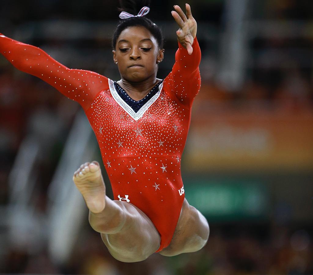 Simone Biles is focused on her jump on the balance beam.