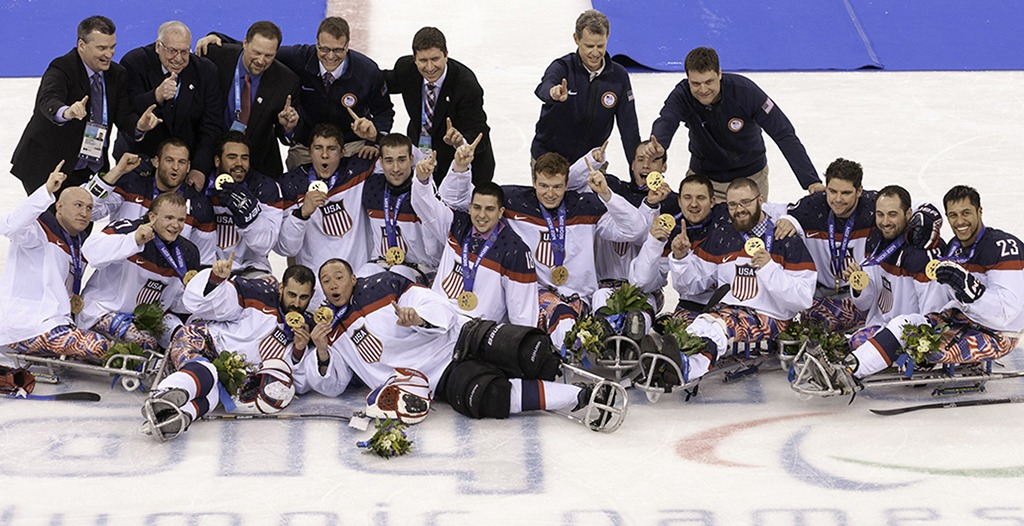 U.S. Sled Hockey Team poses at center ice in celebration.