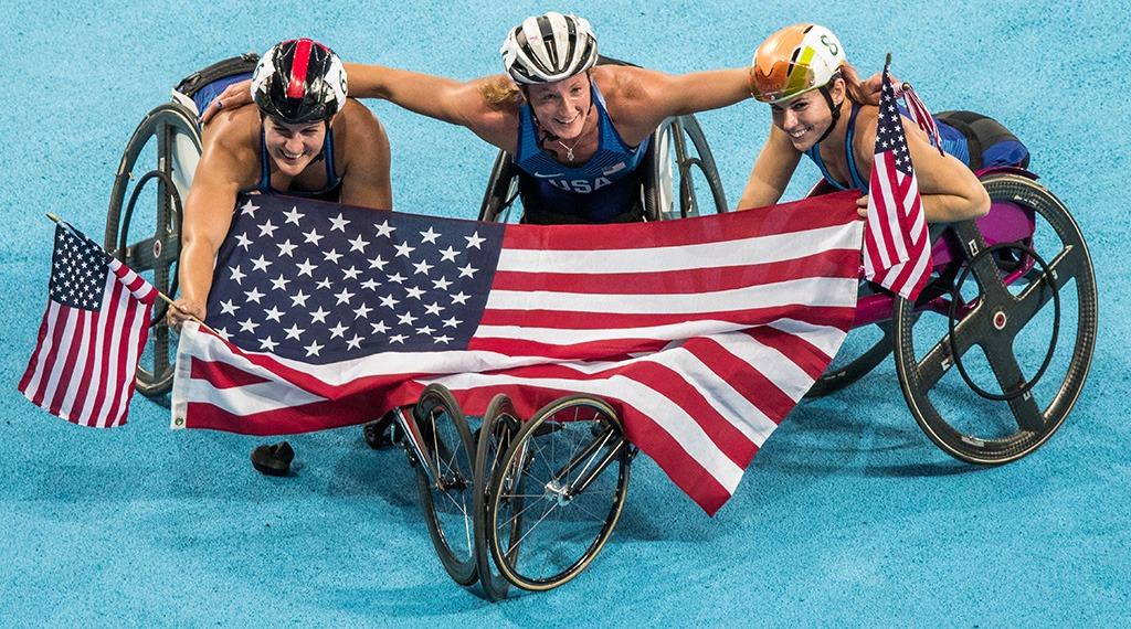 Tatyana McFadden, Amanda McGrory and Chelsie McClammer drape an American flag across their racing wheelchairs.