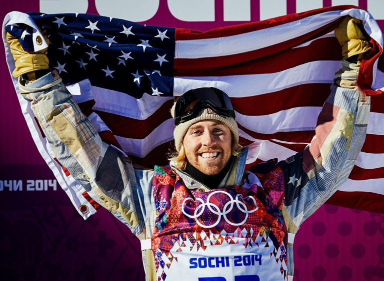 Sage Kotsenburg holds aloft an American flag in celebration