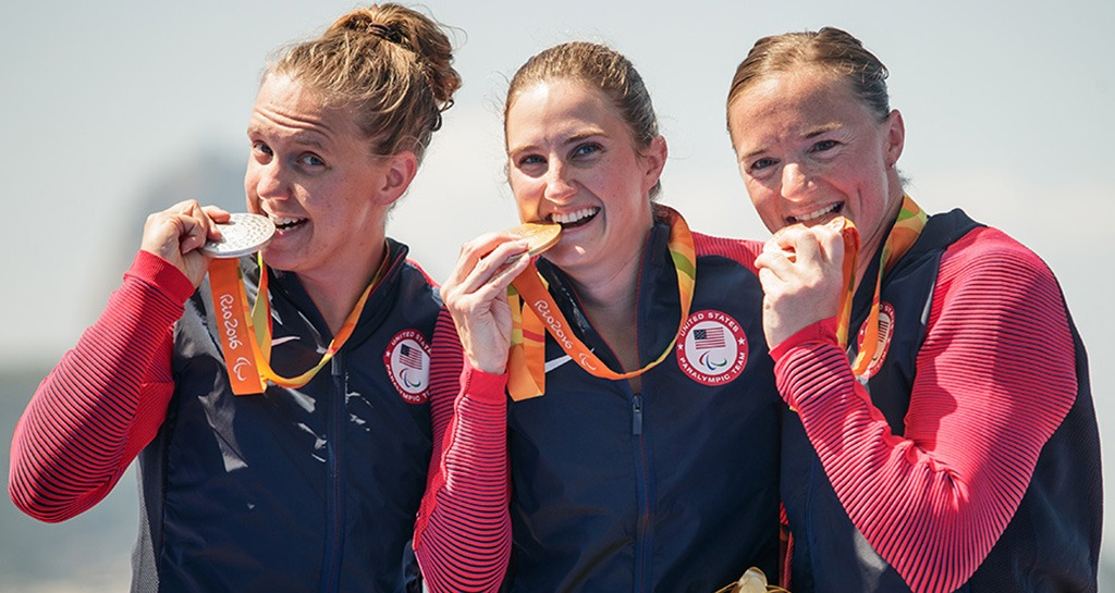Alyssa Seely, Hailey Danisewicz and Melissa Stockwell pose while biting their medals.