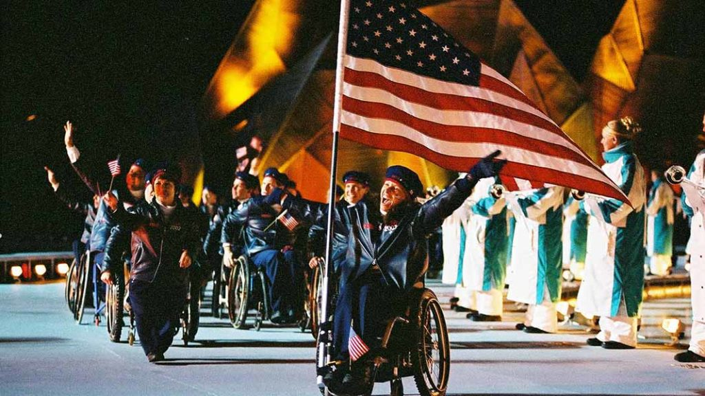 In her wheelchair, Candace Cable carries the U.S. flag into the stadium, with her left arm raised
