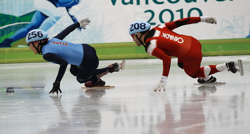 Apolo Anton Ohno has his left hand on the ice as he makes the turn