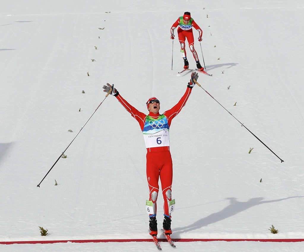 Skier Bill Demong raises his arms as he crosses the finish line