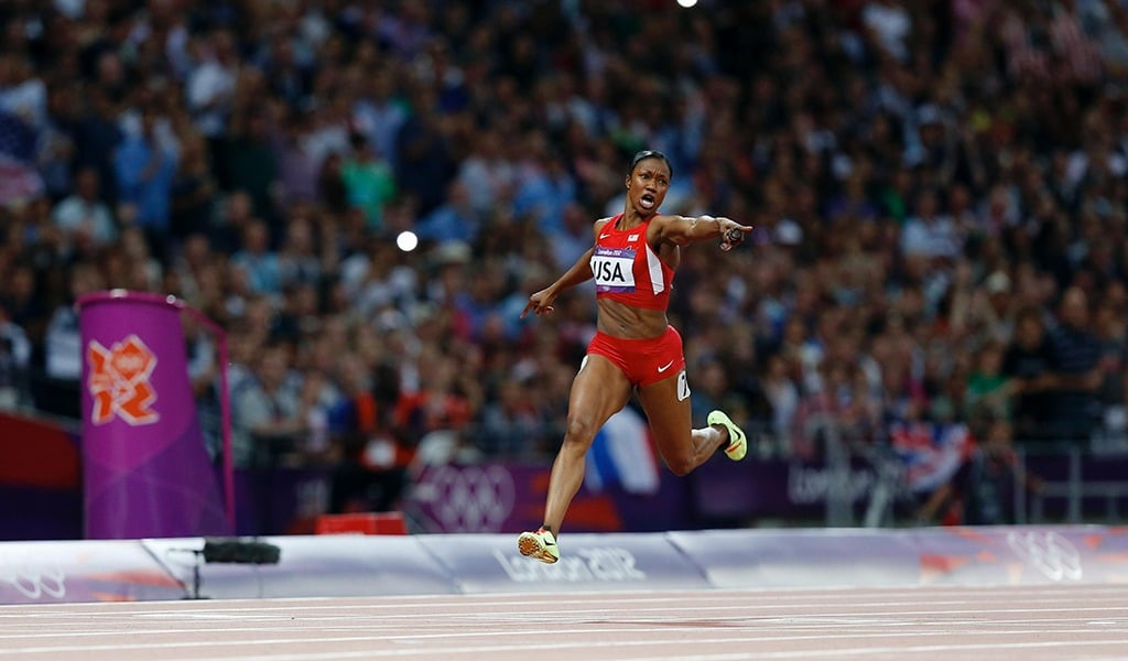 As she crosses the finish line to set a world record in the women's 4x100 relay, Carmelita Jeter points her baton at the timing clock