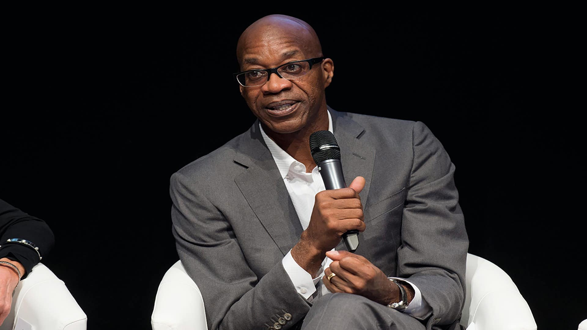 Edwin Moses holds a microphone and speaks