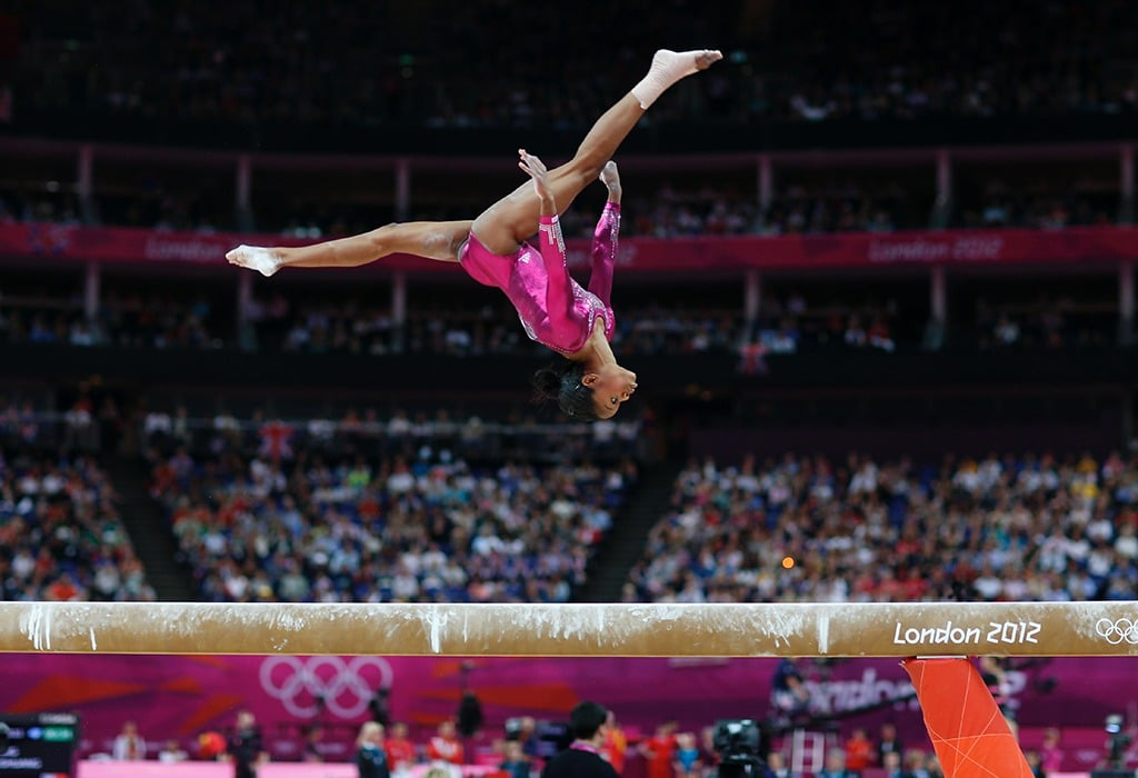 Gabby Douglas is in the air doing a flip on the balance beam