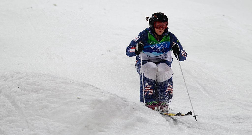 Skier Hannah Kearney stays low as she goes through the moguls