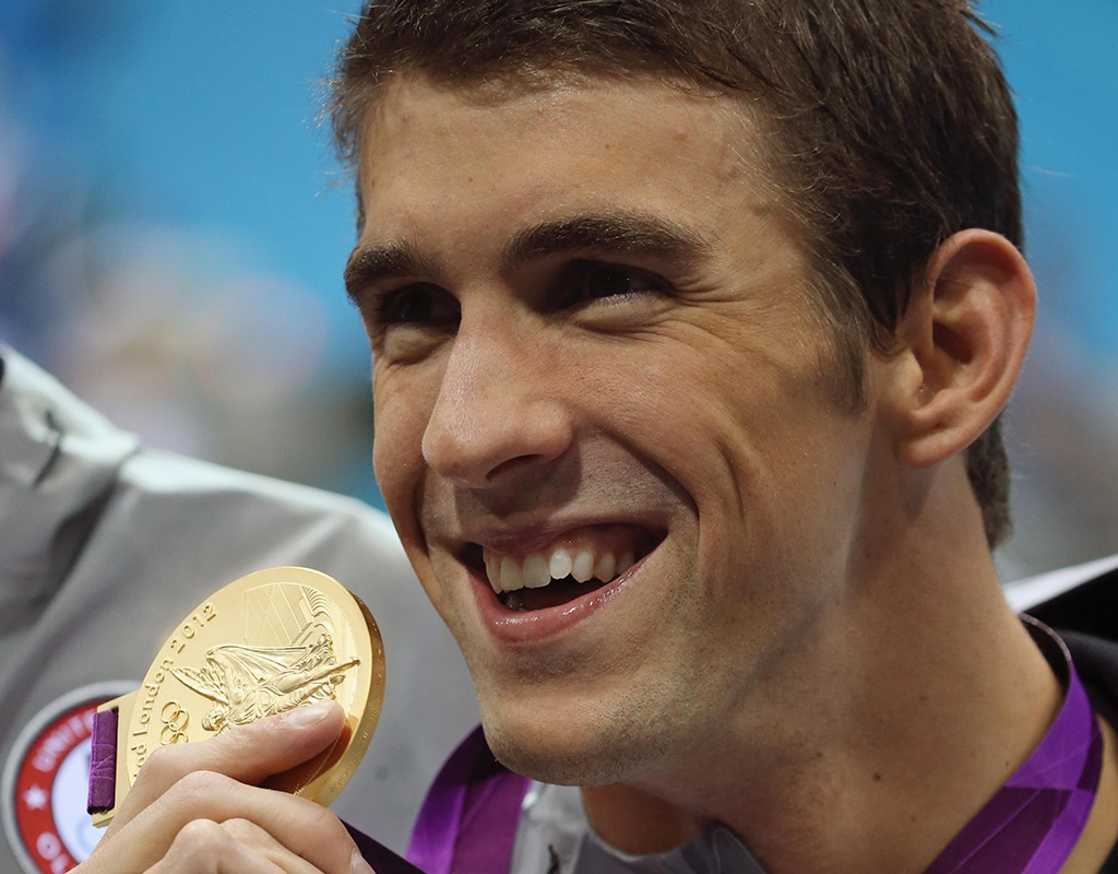 Michael Phelps smiles as he poses with a gold medal