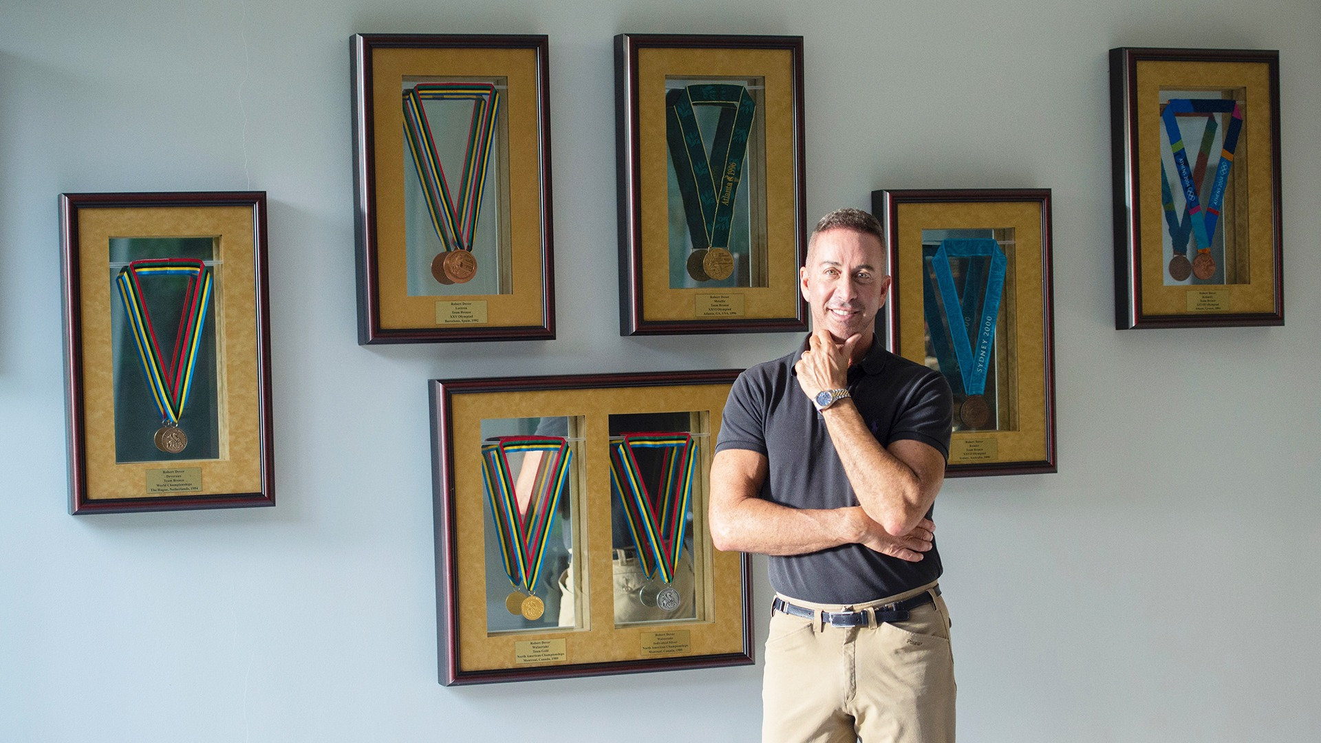 Robert Dover poses in front of his framed medals