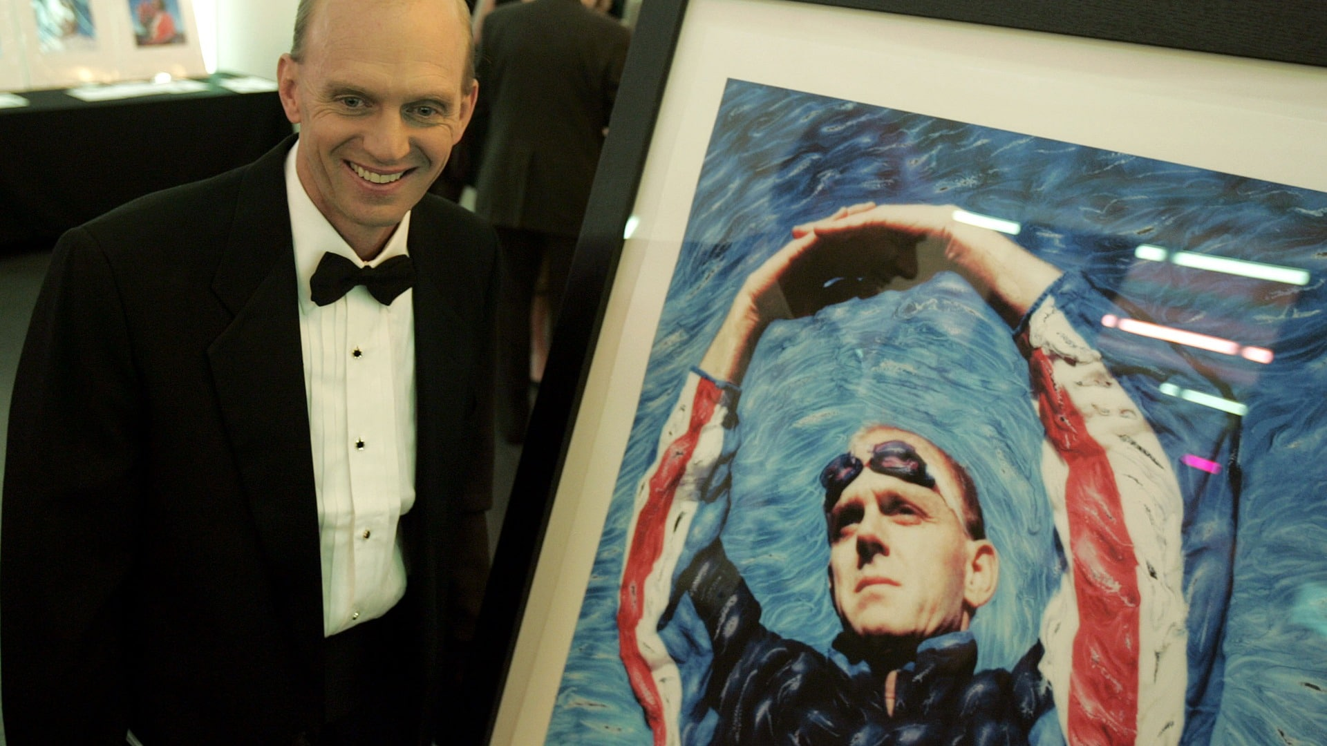 Rowdy Gaines in a tuxedo standing next to a portrait from his swimming career