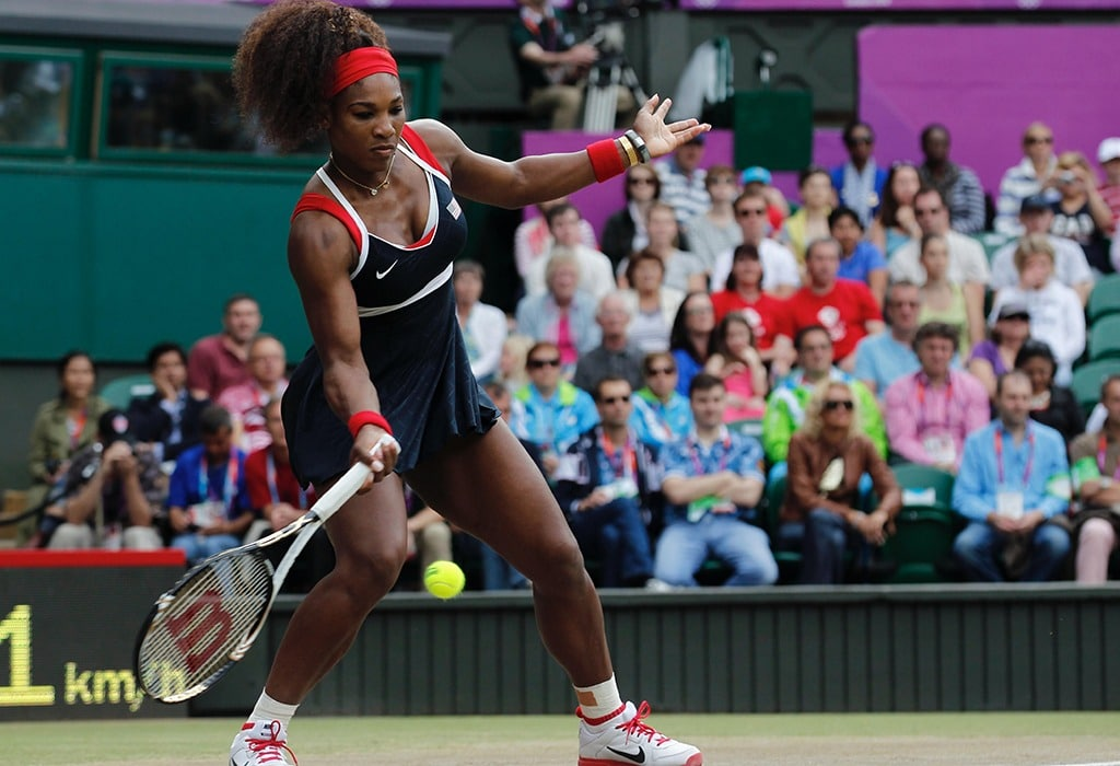 Serena Williams swings and hits a forehand