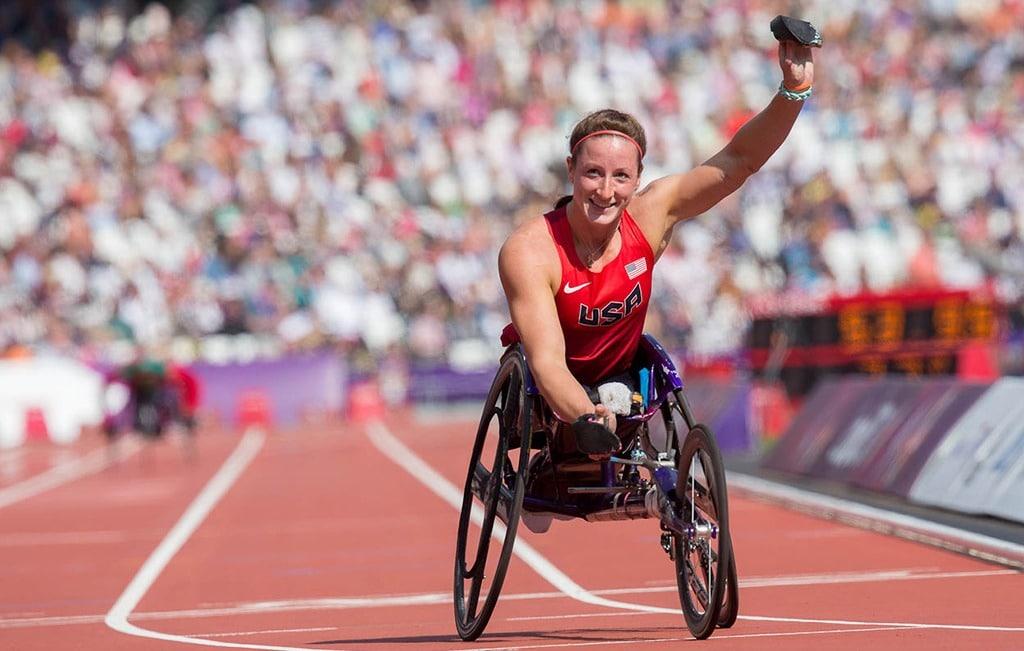Tatyana McFadden raises her left arm to celebrate winning a race