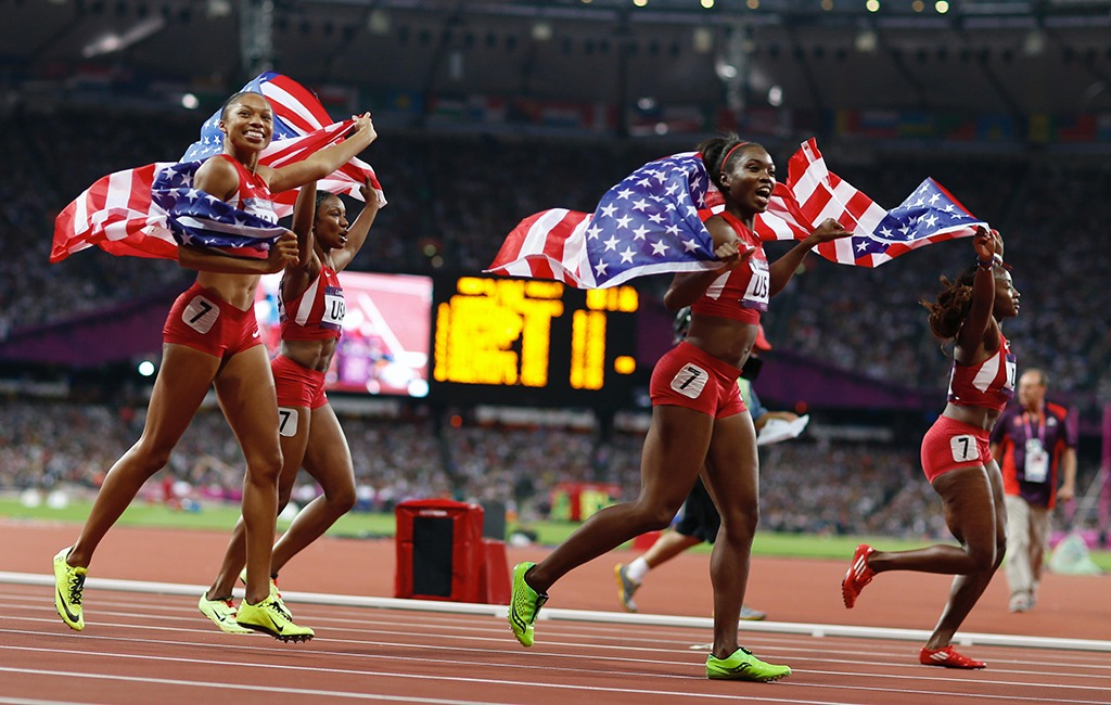The members of the U.S. women's 4x100 relay team run around the track with flag across their shoulders to celebrate