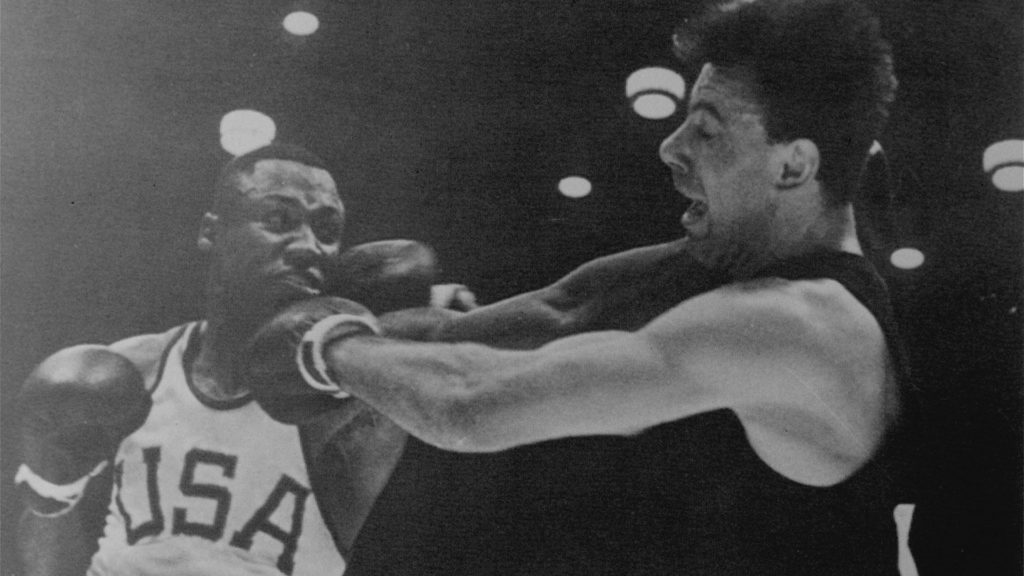 Joe Frazier is punching with his left fish and has his right arm cocked and ready to punch German Hans Huber in the gold-medal bout.