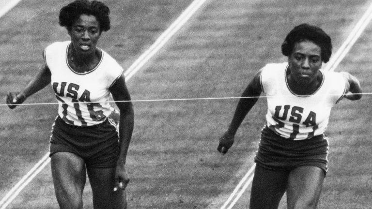 Wyomia Tyus leans forward to edge teammate Edith McGuire at the finish line