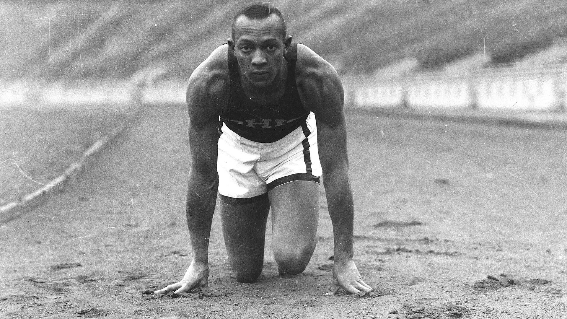 Jesse Owens poses in a crouch on the track at Ohio State