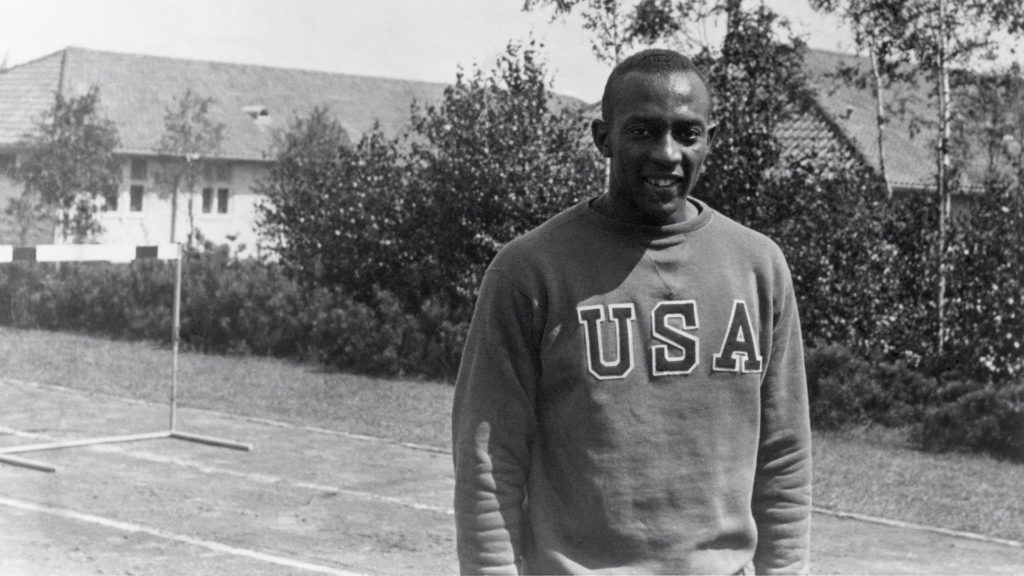 Jesse Owens poses weating a USA sweatshirt in the Olympic Village
