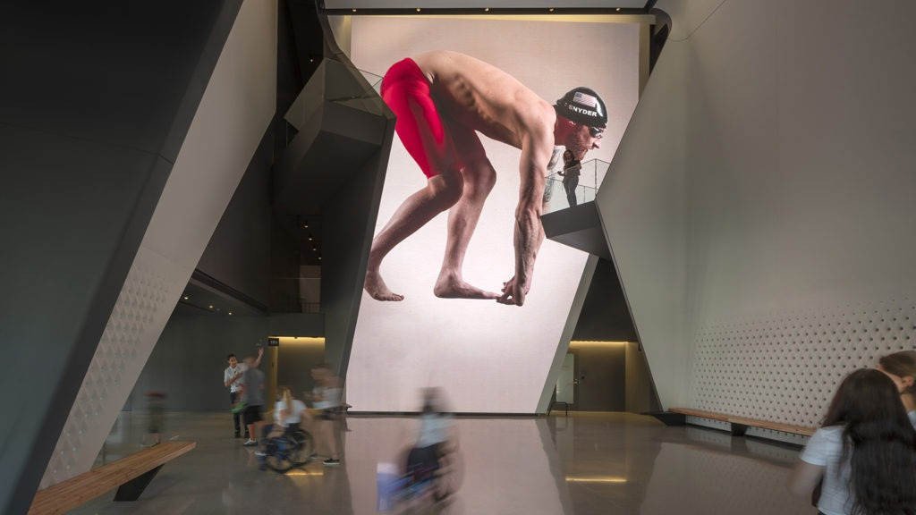 Paralympic swimming champion Brad Snyder is featured on the 40-foot LED wall in the Museum atrium.