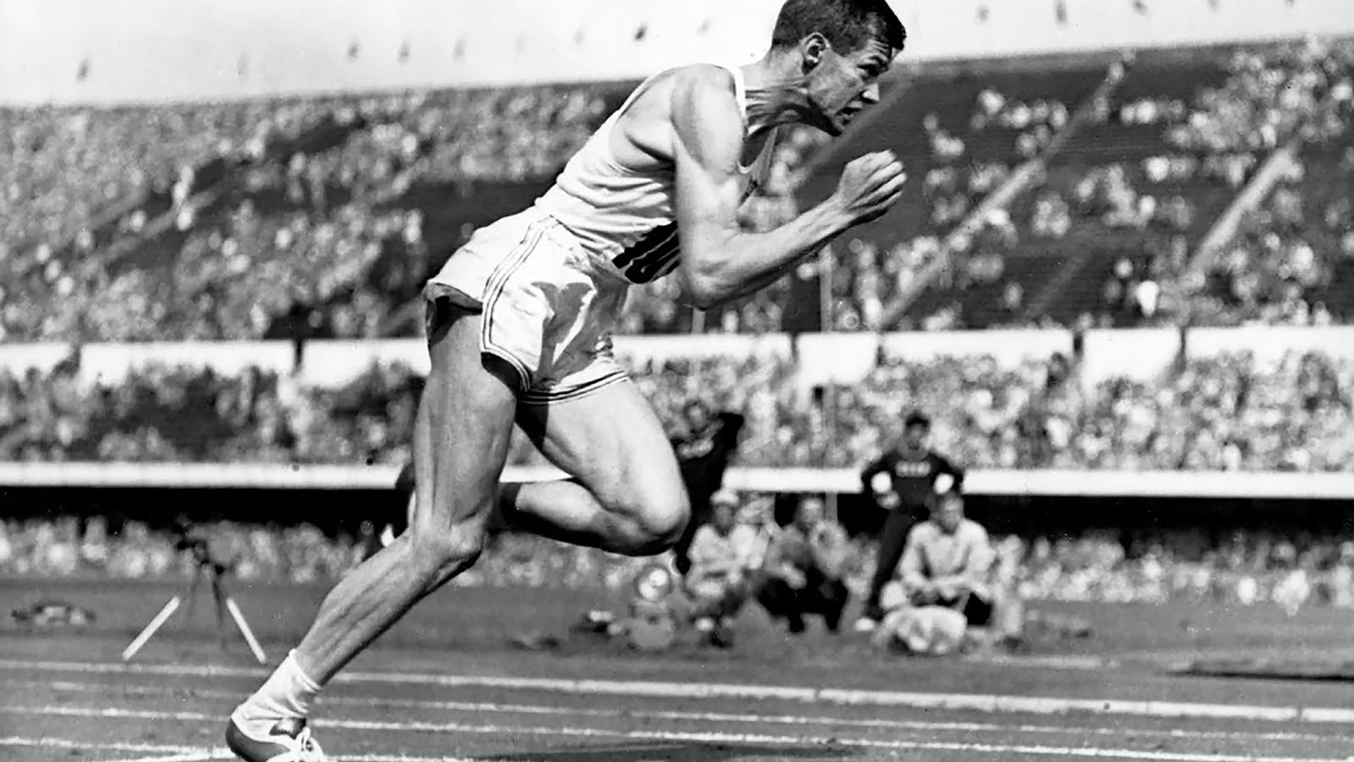Charlie Moore pumps his arms as he sprints around the track