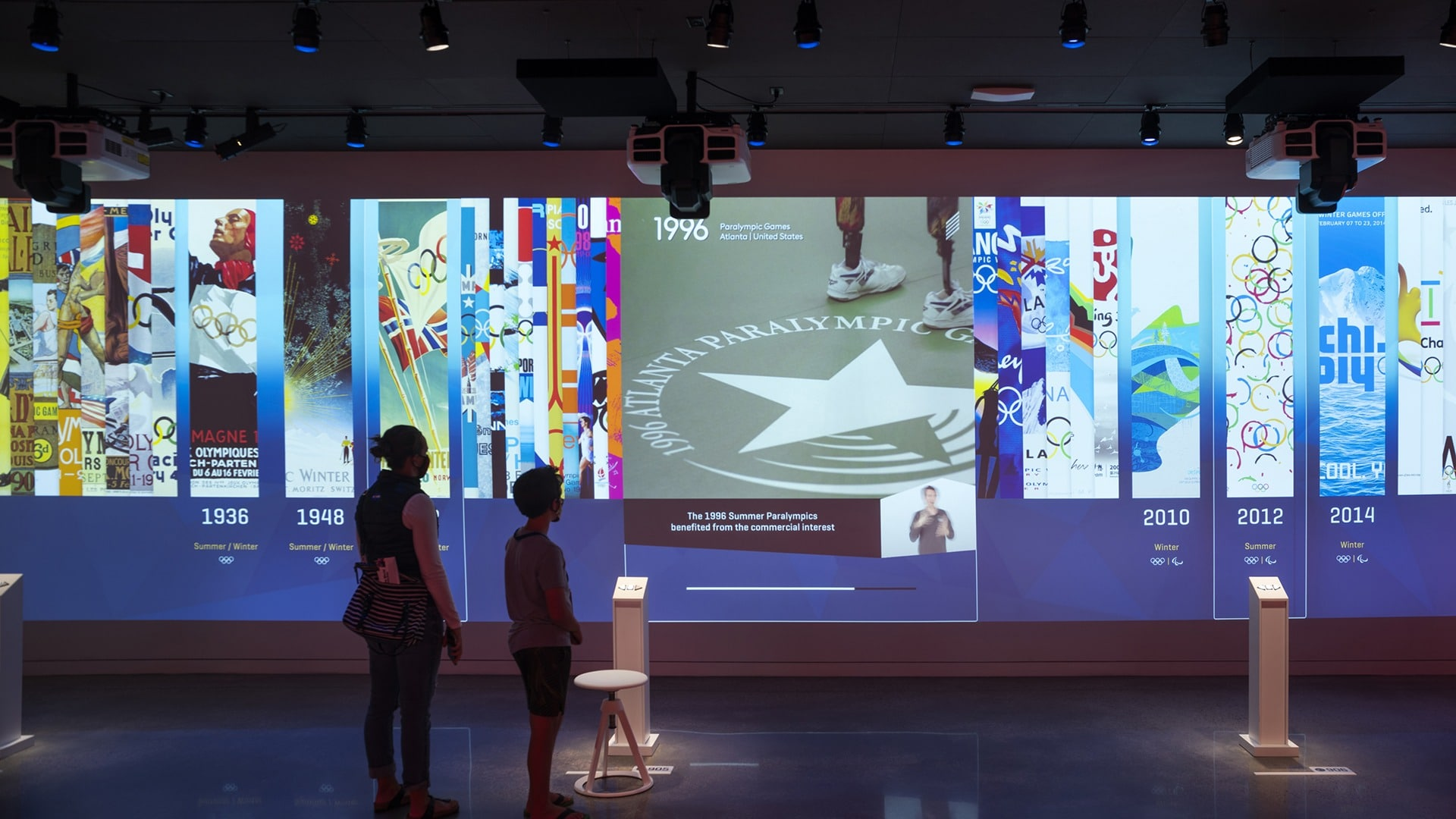 Guests view a digital exhibit of posters from Olympic and Paralympic Games
