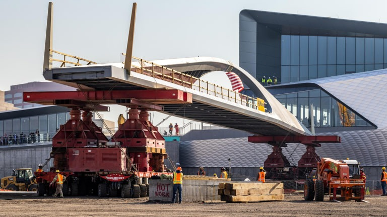 Heavy construction equipment helps move the 250-foot bridge into place.