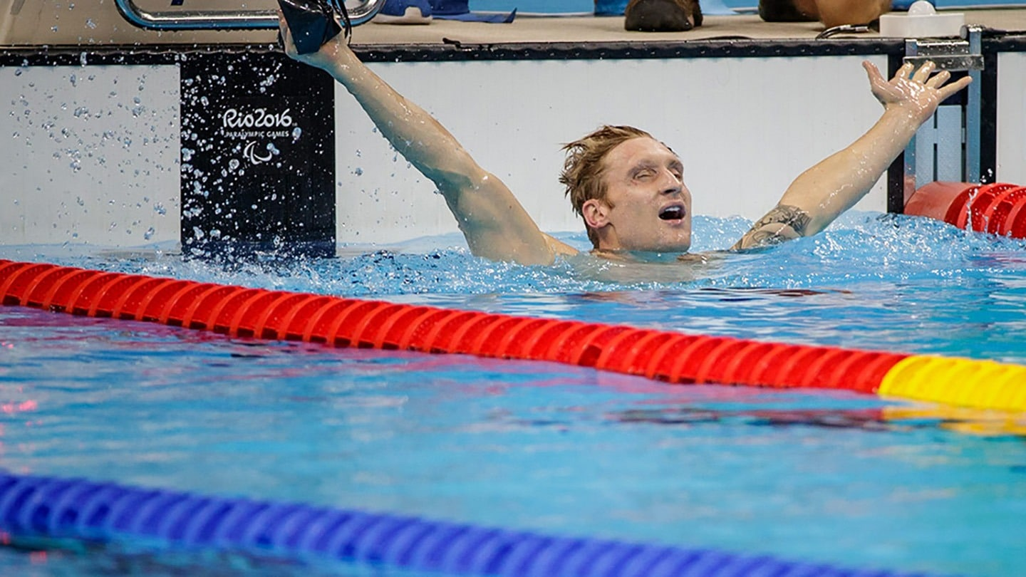 Brad Snyder exults upon winning gold, raising both of his arms in the air.