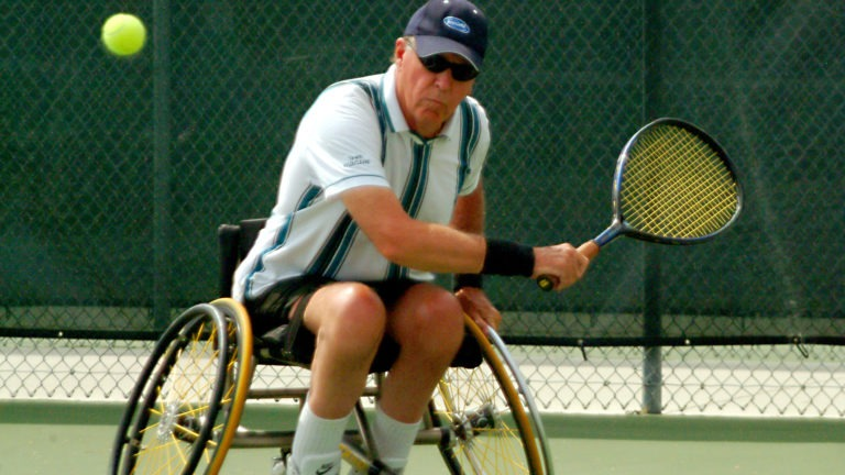 As the tennis ball approaches, Bruce Karr steadies his wheelchair and gets ready to swat a backhand.