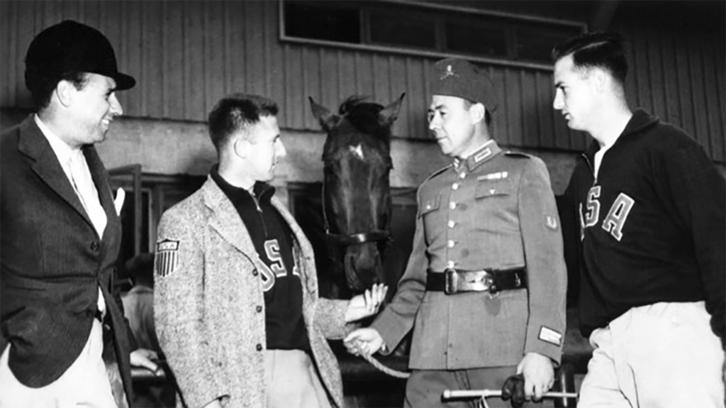 Colonel John Russell speaks with two Portuguese riders and an American teammate at the Helsinki 1952 Olympic Games.