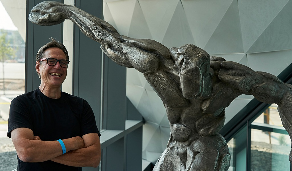 1984 U.S. Olympic fencer Peter Schifrin stands next to his sculpture Olympus Within