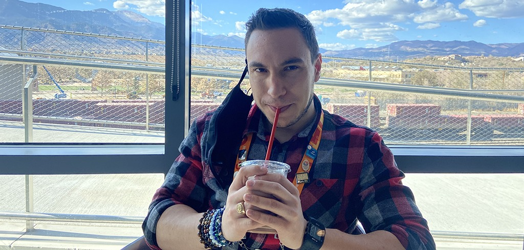 Museum team member Tyler Carter enjoys a TC Special chocolate milkshake inthe Flame Cafe, with Pikes Peak in the Rocky Mountains in the background.