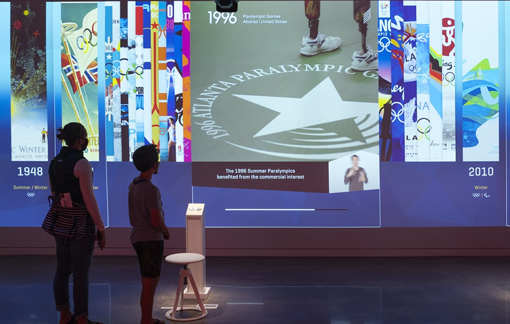 Guests examine a timeline of current events compared to an Olympic and Paralympic timeline