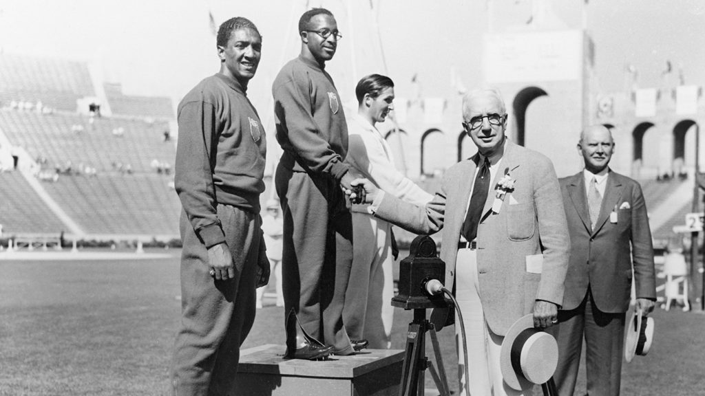 Eddie Tolan proudly stands atop the podium for the medal presentation for the 100 meter race at Los Angeles 1932