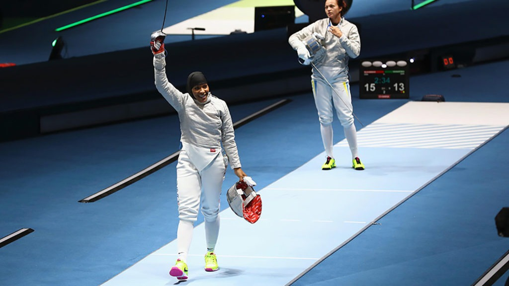 Ibtihaj Muhammad smiles as she takes off her mask and raises her sabre in victory