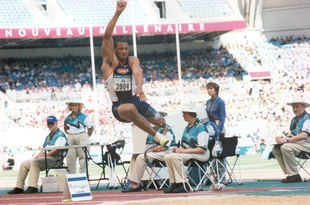 John Register soars in the air and past judges during the long jump at Sydney 2000