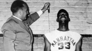 Junius Kellogg cracks a smile as a coach stands on a chair with a measuring tape to show Kellogg's height