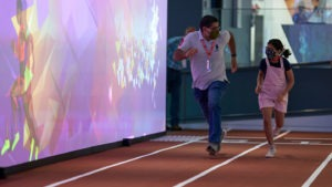A father and his daughter compete in the 30-meter dash interactive exhibit