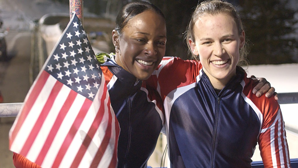 Vonetta Flowers smiles and waves an American flag while posing for a photo with bobsled partner Jill Bakken