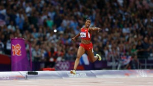 Carmelita Jeter extends her left arm hoding the baton and points at the world-record time on a scoreboard