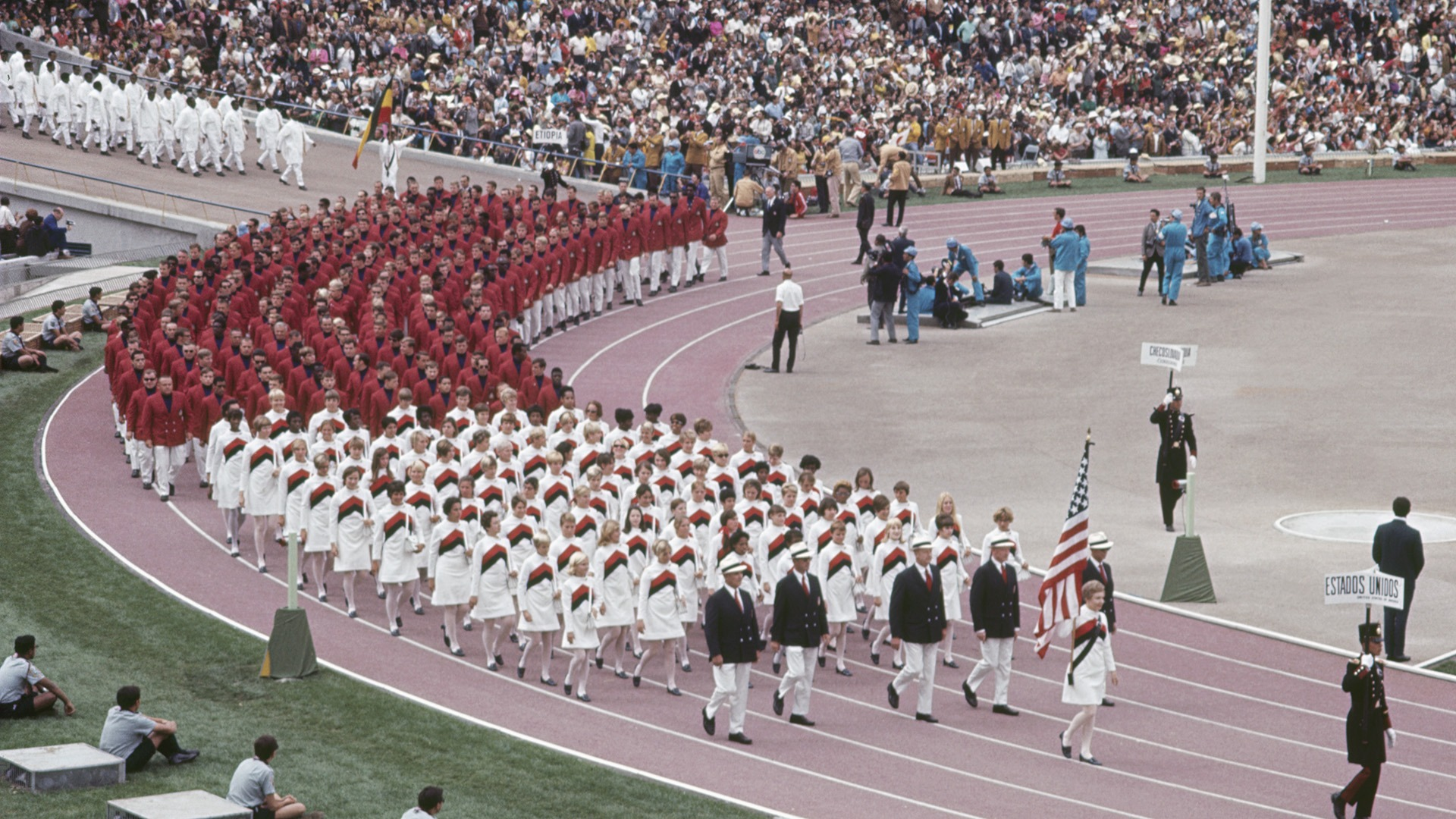 Jan York-Romary is the flag bearer leading Team USA aroudn the track at the Mexico City 1968 Opening Ceremony
