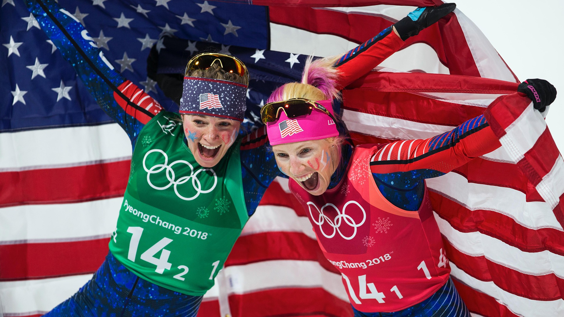 Kikkan Randall (right) and Jessie Diggins hold aloft an American gflag and celebrate their gold medal