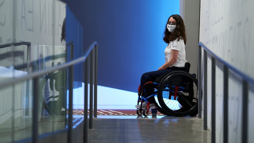 McKenna Geer, sitting in her wheelchair, poses for a photo in the Museum