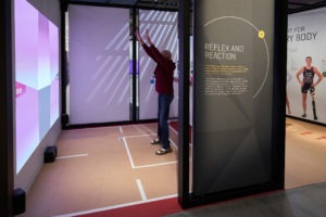 Man enjoys react exhibit at United States Olympic and Paralympic Museum.