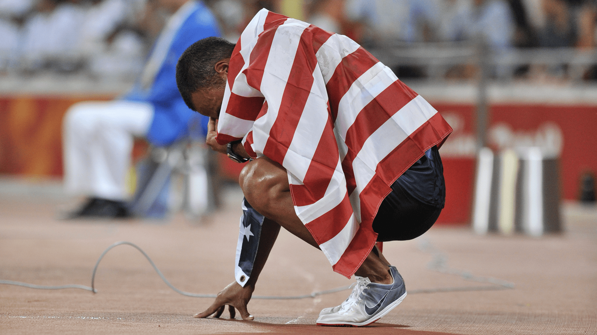 Bryan Clay kneels, overwhelmed with emotion by his victory